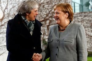 British Prime Minister Theresa May (left) being welcomed by German Chancellor Angela Merkel in Berlin yesterday. Mrs May has travelled to the European continent in a bid to shore up support to save her Brexit deal, which has come under attack from he