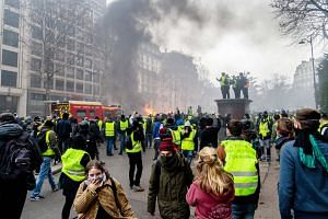 Yellow vest protesters at a rally in Paris last Saturday. French President Emmanuel Macron has been gravely wounded by protests, the accompanying violence - and the panic-driven U-turns in government policy, says the writer.