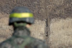 North Korean soldiers move to inspect a dismantled guard post inside the Demilitarised Zone, while a South Korean soldier stands guard in the central section of the border on Dec 12, 2018.