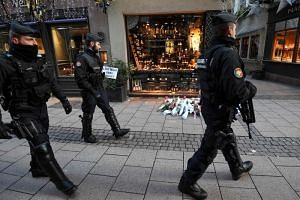 French gendarmes walk past flowers and candles laid in the street in tribute to the victims of a deadly shooting in central Strasbourg, on Dec 13, 2018.