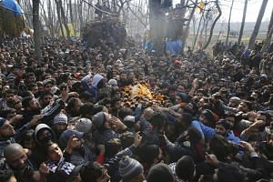 Kashmiri Muslims carry the body of slain militant Zahoor Ahmad Thoker from a window at Sirnoo in Pulwama, Kashmir, on Dec 15, 2018.
