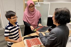 Madam Fazilah, accompanied by her son, at the HDB Hub in Toa Payoh collecting the keys to their new home on Dec 13, 2018.