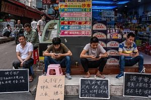 Employees from a garment factory in Guangzhou sitting behind handwritten signs that say in Chinese, ''Looking for customers