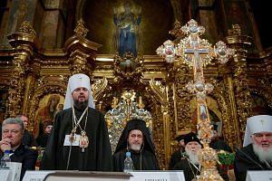 Metropolitan Epifaniy (standing), elected as leader of Ukraine's newly independent Church, speaking at the St Sophia Cathedral in Kiev, Ukraine, last Saturday. Also present was Ukrainian President Petro Poroshenko (left).