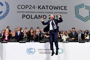 COP24 president Michal Kurtyka jumps at the end of the final session of the COP24 summit on climate change in Katowice, southern Poland, on Dec 15, 2018.
