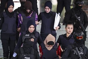 Doan Thi Huong (second left, back) and Siti Aisyah (third left, front), both accused of murdering Kim Jong Nam, being escorted by police officers out of the Shah Alam High Court in Malaysia, on Dec 14, 2018.