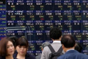 File photo showing pedestrians walking past a stock indicator board of the Tokyo Stock Exchange in Tokyo, on Dec 5, 2018.