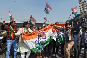 File photo of Indian Congress party supporters holding a Congress party flag as they celebrate in Ahmedabad on Dec 11, 2018.