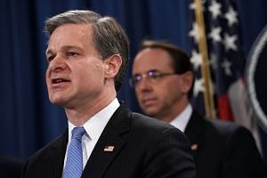 FBI director Christopher Wray (left) speaking at a news conference on two alleged Chinese hackers in Washington.