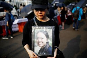A woman with a photo of a relative, one of the 189 people killed in October's Lion Air plane crash in Indonesia. The final report on the crash is due in 10 months' time.