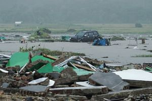 A damaged car and debris left in the wake of the tsunami, which took the lives of more than 220 people and injured over 800 others.