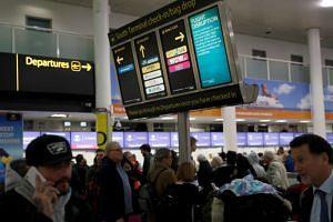 Passengers walk beneath screens displaying travel information in Gatwick Airport, in Crawley, Britain, on Dec 22, 2018.