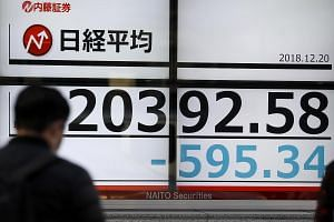 A pedestrian walks past a display showing closing information of Tokyo benchmark Nikkei Stock Average in Tokyo, Japan on Dec 20 2018.
