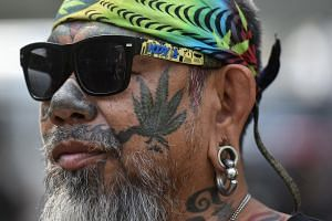 A Thai activist with a marijuana tattoo on his face gathers with others during a campaign for the legalisation of medical marijuana on Nov 20, 2018.