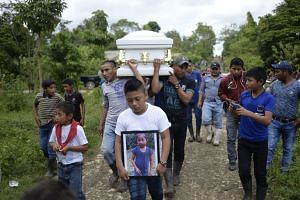 A boy carries a picture of Jakelin as her coffin is taken from Raxruha to the cemetery in San Antonio Secortez.