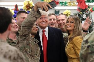 "US President Donald Trump and his wife Melania posing for a wefie with US soldiers during a surprise visit to the Al Asad Air Base in Iraq on Wednesday. About 100 US servicemen and women, some of whom were wearing red ""Make America Great Again"" caps,"