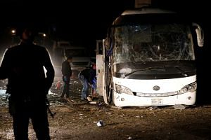 Police officers inspect the scene of the bus blast in Giza, Egypt.