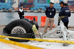 Indonesian forensic policemen stand beside a damaged tyre from the the Lion Air flight JT610 jet at Tanjung Priok port in Jakarta, Indonesia, on Nov 5, 2018.