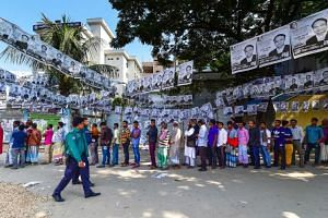 Voters waiting in line beneath election posters at a polling station in Dhaka on Dec 30, 2018.