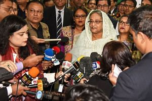 Bangladeshi Prime Minister Sheikh Hasina (in white) speaks to the media after casting her vote at a polling station in Dhaka on Dec 30, 2018. Bangladesh headed to the polls on Dec 30 following a weeks-long campaign that was dominated by deadly violen
