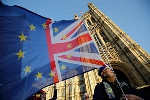 An anti-Brexit activist flies a flag showing the colours of the UK and the EU outside the Houses of Parliament in London, on Dec 11, 2018.
