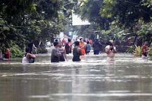 Residents wade along a flooded street in the town of Bulan, Sorsogon province, Philippines on Dec 30, 2018.