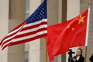 US and Chinese flags flying at the Pentagon in Arlington, Virginia, US.
