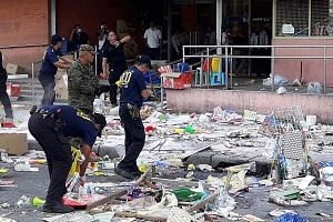 Police gathering evidence outside a shopping mall in Cotabato city, southern Philippines, where an explosion took place on New Year's Eve. A Philippine military official says the attack was probably in retaliation for the deaths of four militants in