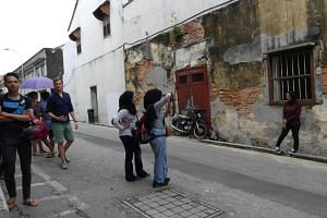 File photo showing visitors taking photos with an old shophouse in George Town, Penang, on Jan 11, 2018.