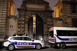 Left: Police in Paris keeping watch outside the chief government spokesman's office on Saturday after protesters forced their way in earlier after breaking down the door (above).