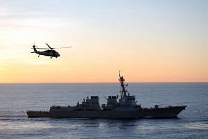 A helicopter flies over to the USS McCampbell after delivering supplies on July 8, 2012.