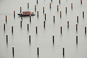 A safety craft manoeuvring its way among pilings at Dover Marina in Britain last Saturday. The port, which operates 120 ferries a day carrying 10,000 lorries, accounts for 17 per cent of Britain's trade in goods. As part of a government exercise yest