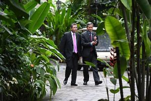 Left: Foreign Minister Vivian Balakrishnan and Malaysian Foreign Minister Saifuddin Abdullah arriving at The Villa in the Singapore Botanic Gardens' Ginger Garden, where they had lunch (above) yesterday. The meeting shows there is political will on b