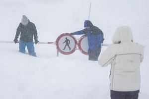 People standing in front of snow-covered road signs during a snowstorm at the Arlberg Pass in St Christoph am Arlberg, Austria.