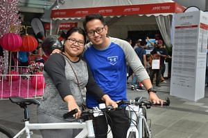 Engineer Bryan Phyo, 33, and his wife Michelle Myat, 35, posing with the road bicycles they redeemed for being the first two people in the queue to register for OCBC Cycle.