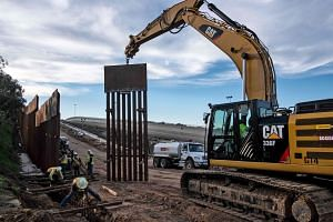 A construction crew replacing a section of the US-Mexico border fence in Tijuana, Mexico, on Wednesday. US President Donald Trump wants $7.7 billion to build a wall to keep out illegal immigrants from Mexico.