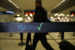 Travellers go through the TSA PreCheck security point at Miami International Airport in a file photo.