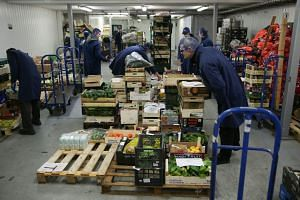 Workers prepare boxes of fresh fruit and vegetables ahead of distribution from the warehouse of Natoora, a fruit and vegetable distribution company, in south London, on Dec 5, 2018.
