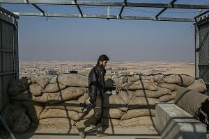 A fighter with the US-backed Syrian Democratic Forces near Manbij, Syria, last month. After media reports suggested the departure of US forces had begun, the Pentagon later said no troops had yet withdrawn and stressed that the battle against ISIS wa