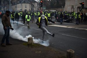"""A protester kicks a tear gas canister during an anti-government demonstration called by the """"Yellow Vest"""" movement in Bourges, central France, on Jan 12, 2019."""
