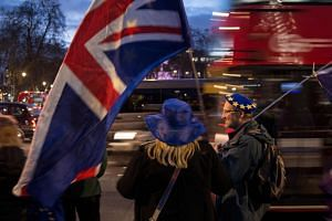 Anti-Brexit supporters hold flags as they demonstrate outside the Houses of Parliament on Jan 14, 2019.