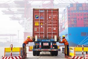 Workers prepare a container at Qingdao port in Shandong. China's December exports fell 4.4 per cent from a year earlier, with demand in most of its major markets weakening.