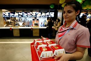 A McDonald's employee holds a tray of Big Mac burgers at an outlet in central Moscow, Russia, on Jan 31, 2017.