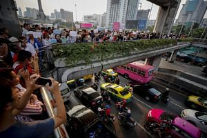 Thai pro-democracy activists on an overpass displaying placards during a rally in Bangkok, Thailand, on Jan 6, 2019.
