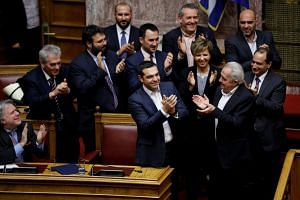 Tsipras and members of his government applaud after winning a confidence vote in Athens, Greece.