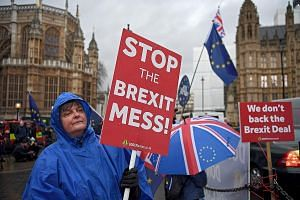 Protesters outside the Houses of Parliament in London on Wednesday, after Mrs May's Brexit deal was crushed by Parliament in the biggest defeat for a British leader in modern political history. British Prime Minister Theresa May listening as Environm