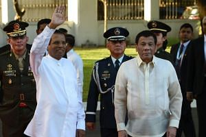 Sri Lankan President Maithripala Sirisena (left) waves to members of the media as Philippine President Rodrigo Duterte looks on during a welcoming ceremony at the Malacanang Palace grounds in Manila on Jan 16, 2019.