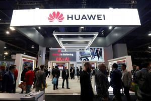Attendees pass by a Huawei booth during the 2019 CES event in Las Vegas, US, Jan 9, 2019.
