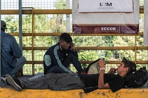 An Honduran migrant heading to the US rests after receiving an identification bracelet from Mexican migration authorities.