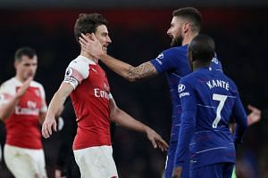Arsenal's Laurent Koscielny with Chelsea's Olivier Giroud at the end of the match.